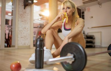Athlete eating banana on a break in a gym.